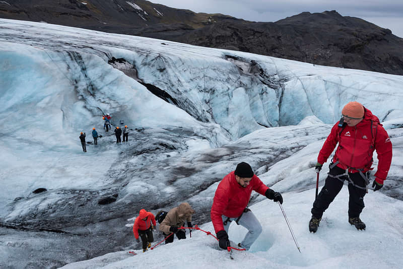 Group of people hiking and climbing on a glacier