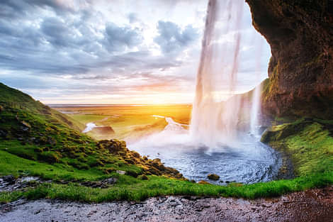 Walking behind a waterfall in summer with sun on horizon