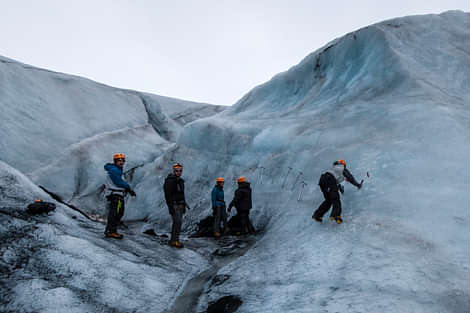 People hiking and climbing on a glacier
