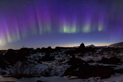 Northern Lights over cliff in Iceland