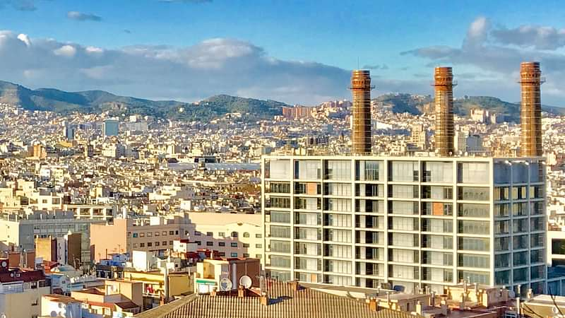 Panoramic view from the top of the hill over Barcelona with thousands of buildings. Big office building with three chimneys in the front.