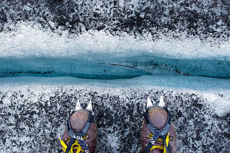 Glacier hiking, hiking shoes with crampons, looking down a crevasse, blue ice