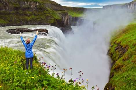 Gullfoss in Iceland with happy woman in front