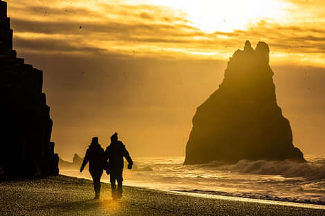 People walking along the black sand beach during sunset