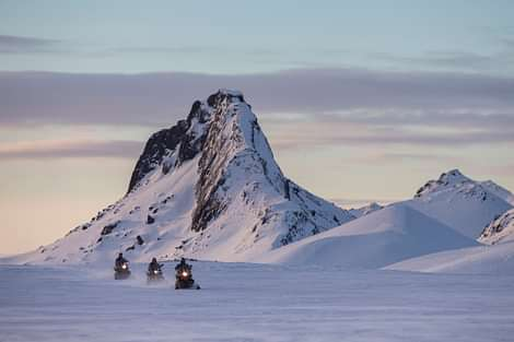 Snowmobiling in Langjökull Glacier in Iceland with cliff behind