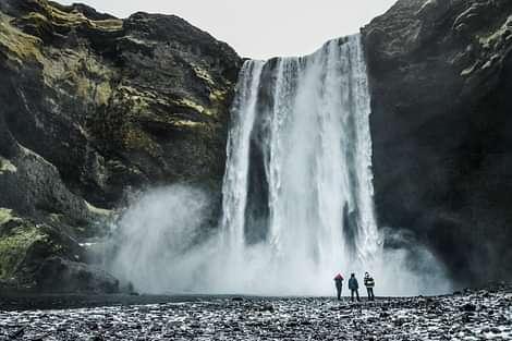 People standing next to Skogafoss waterfall