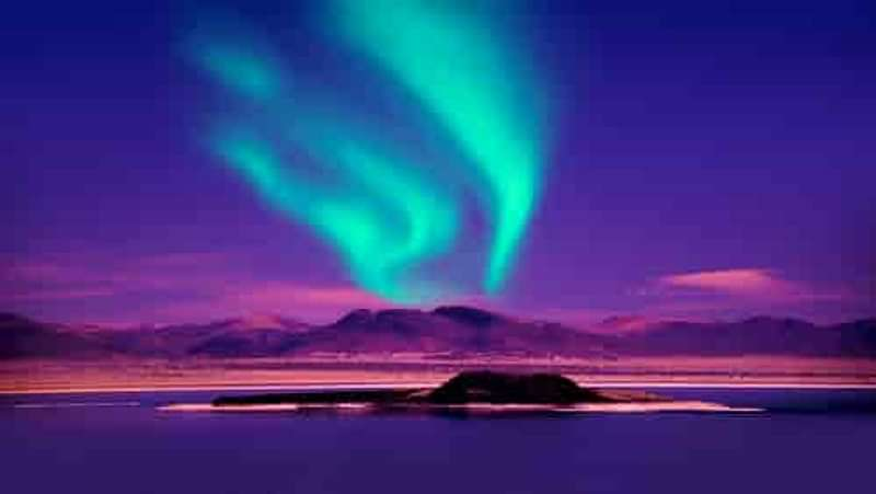 Northern Lights over Mountain overlooking lake in Iceland