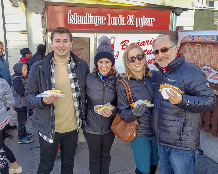 A family enjoying the Icelandic hot dog at the original food stall which dates from 1937