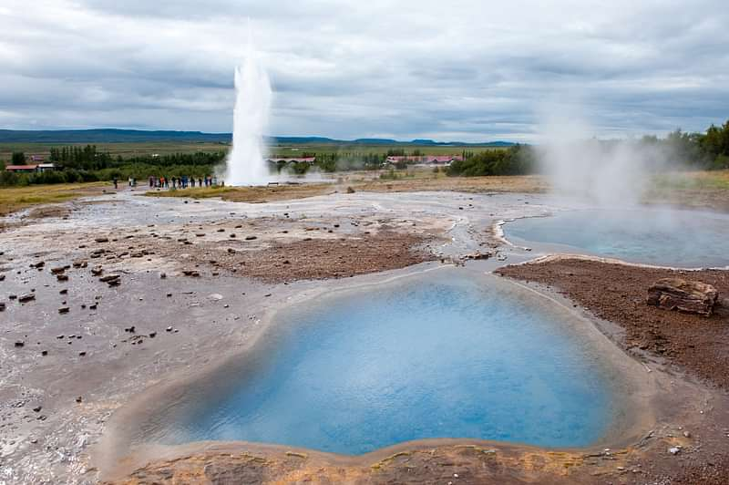 Blue hot spring with Geysir in distance