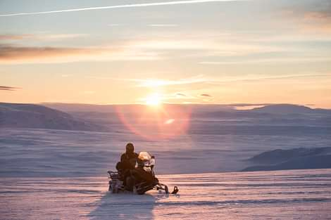 Snowmobiling in Langjökull Glacier in Iceland at sunset